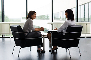 Two-Women-Sitting-in-Chairs